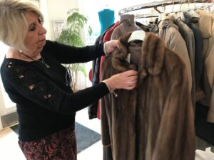 Anita viser en pelsfrakke frem i genbrugsbutikken i Valby. Dem er der meget få, der køber, fordi der er kommet mere fokus på dyrevelfærd, fortæller hun.